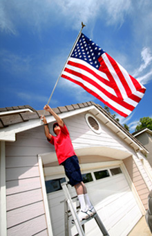 Photo of man putting up a flag on a house