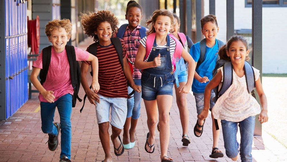 Group of children running towards camera wearing book bags