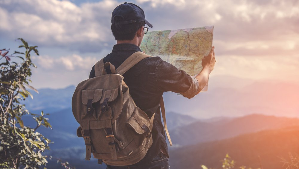 The back of a man wearing a backpack, holding up a map as he's facing the lookout towards rolling mountains