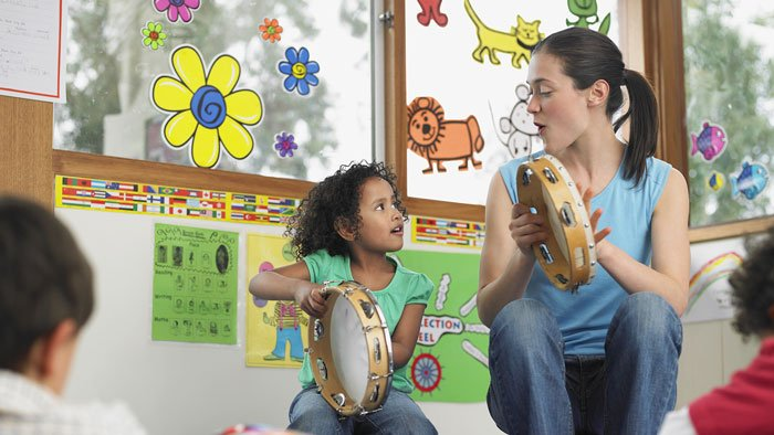 Teacher sits next to small child holding tambourine and smiling in front of class