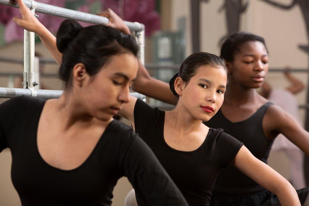 Three teen ballet dancers at the barre