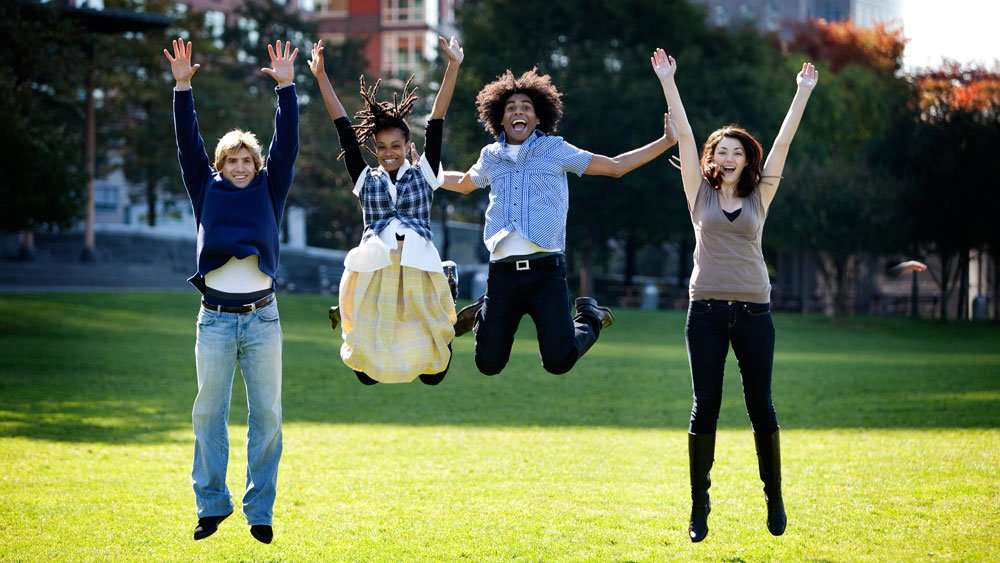 Two girls and two guys of different ethnicities jumping in the air with their hands up