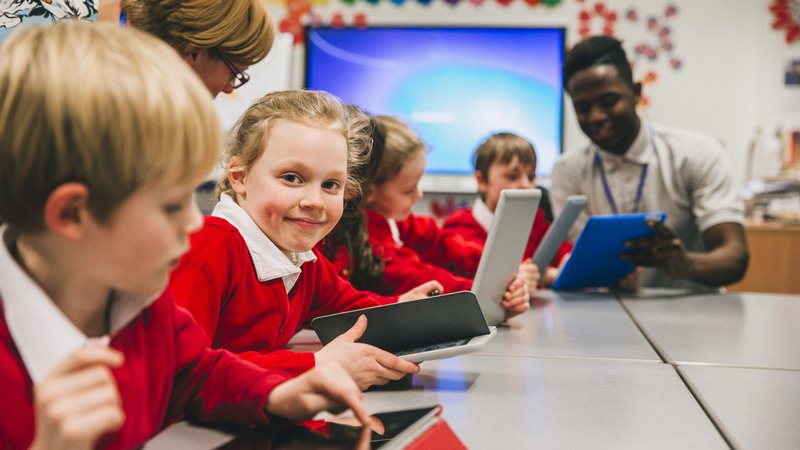Young girl with dimples faces the camera smiling while sitting at desk with other young kids all holding laptops with two teachers assisting