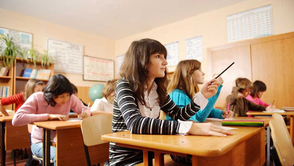 Teen girl sitting at desk in classroom surrounded by others is looking up and pointing with a pen or pencil