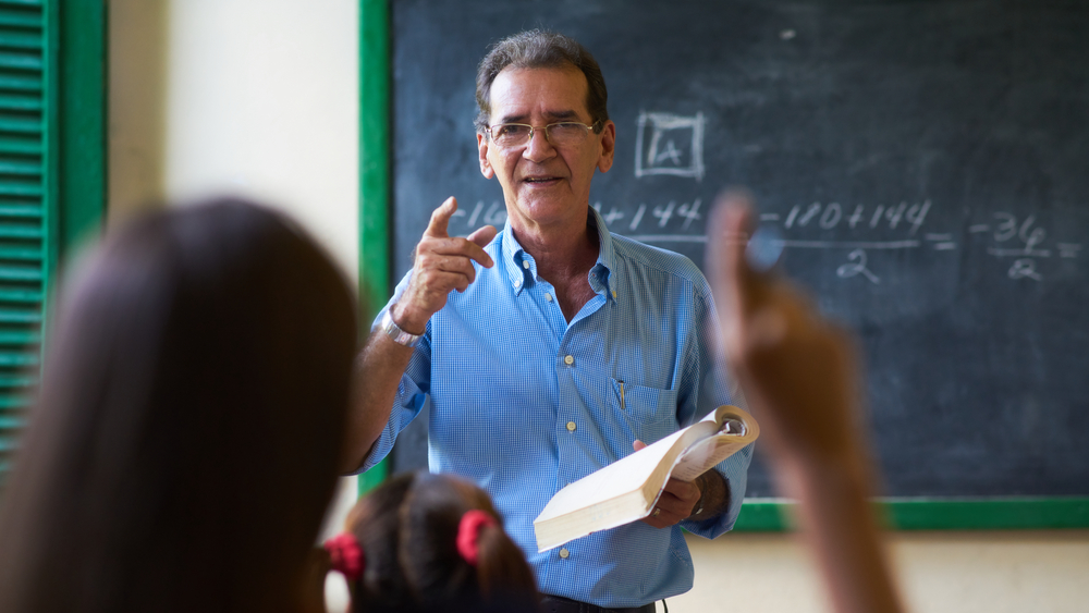 Male teacher stands in background near chalkboard pointing at student raising her hand in the foreground