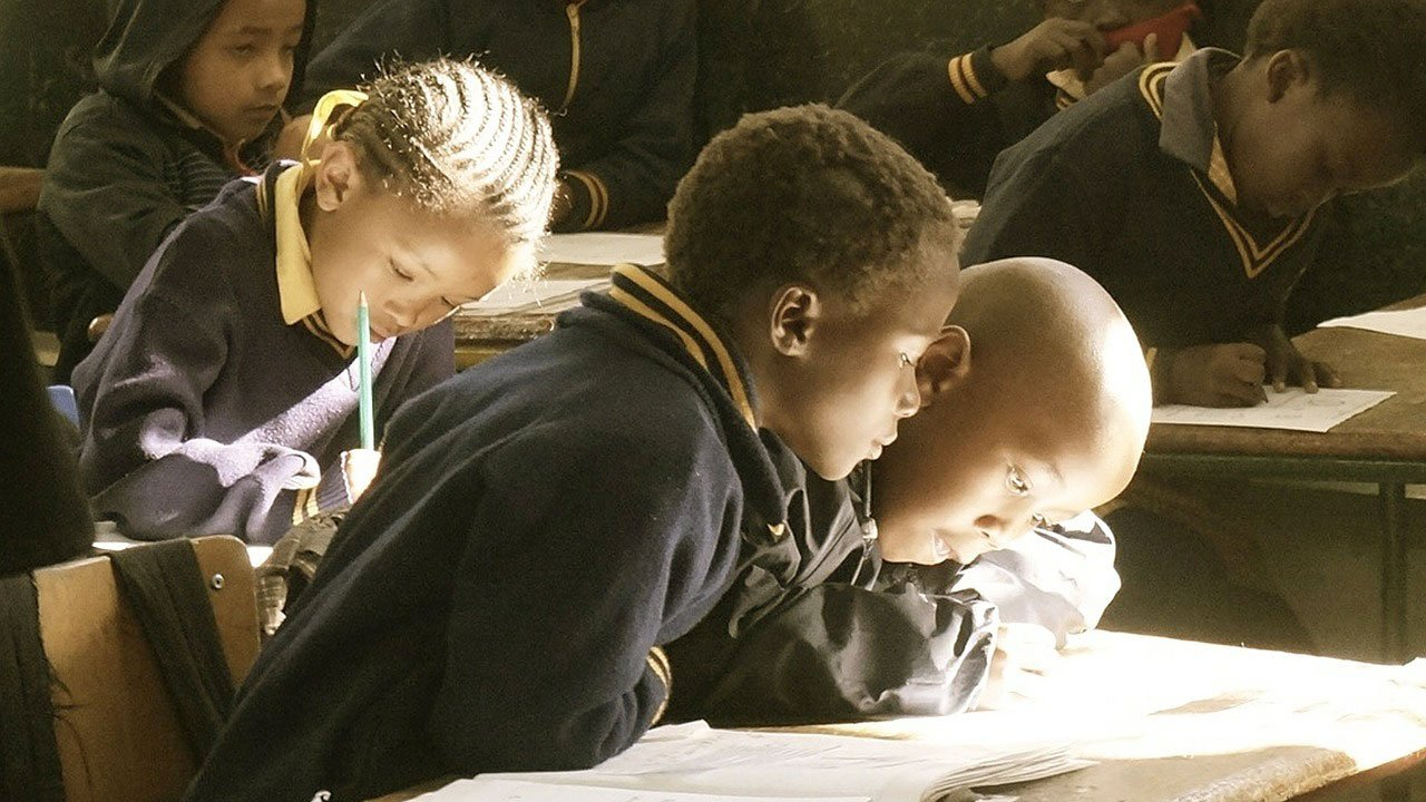 Two young boys sit side by side at a desk in a classroom reading a book