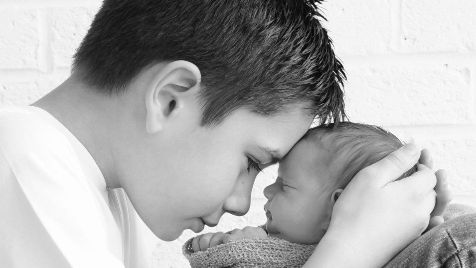Young boy holds newborn baby close too his face