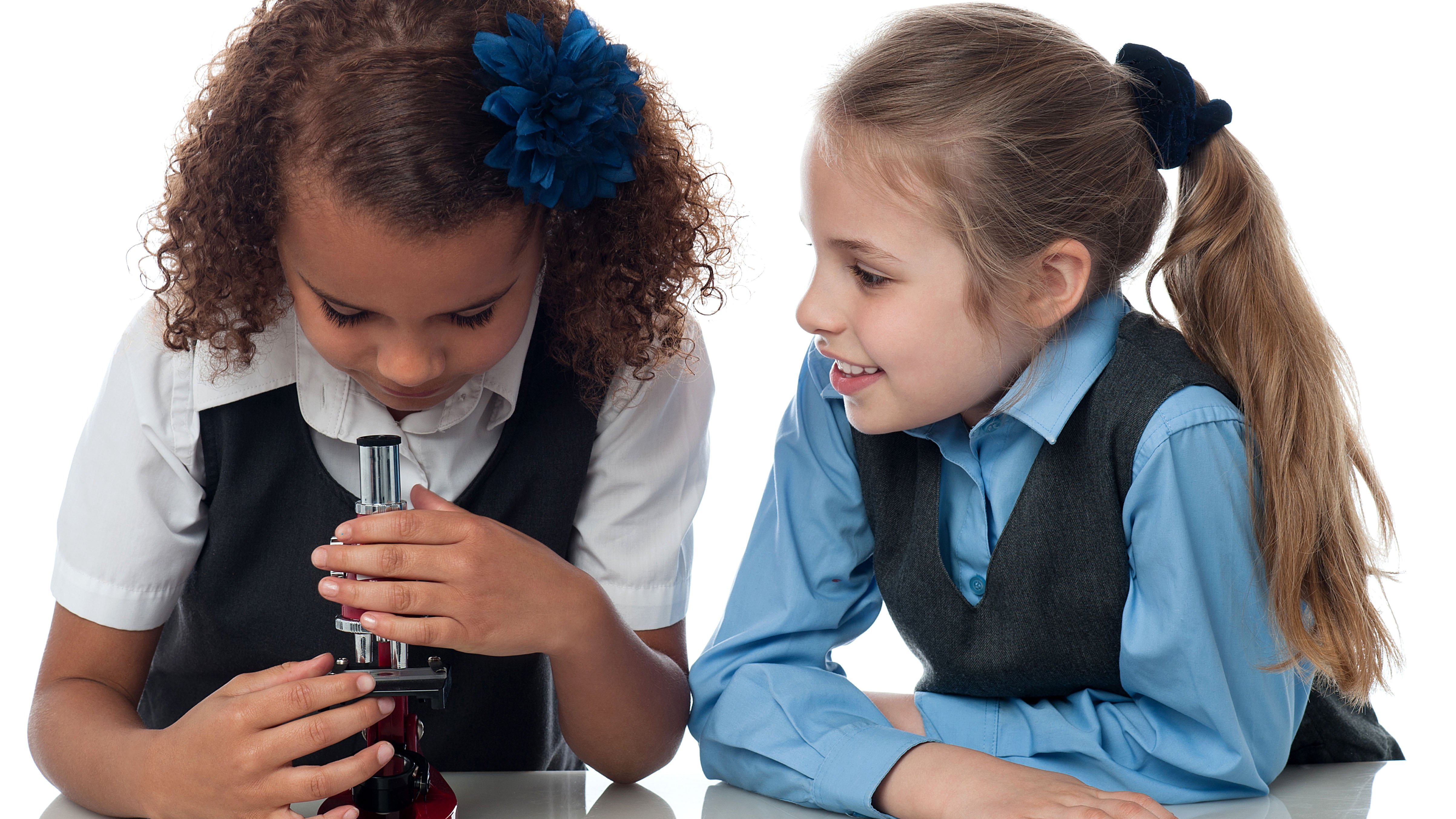 Two school girls, one looking in a microscope while the other watches her smiling