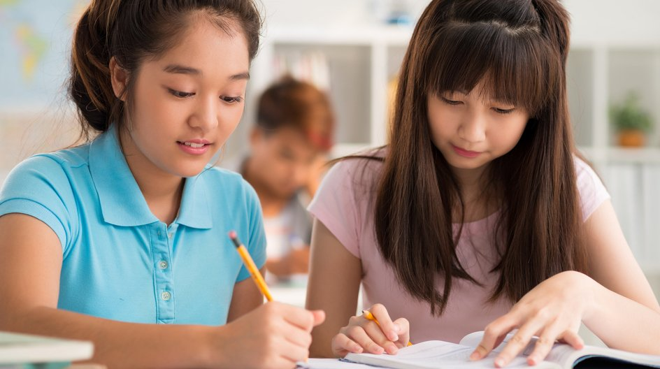 Two girls holding pencils looking down as one writes in a book