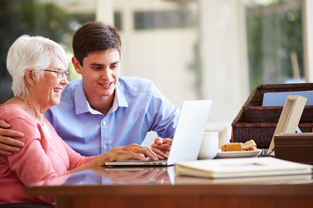Older woman using a computer and young man sitting by her side looking at the screen