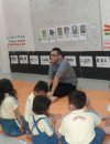 Male teacher sitting on mat in front of a class full of small kids