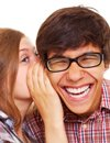 Photo of woman whispering in to a man's ear while he laughs