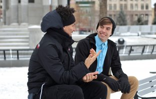 Two young men sit on a bench surrounded by snow, one man is pointing and the other man is smiling