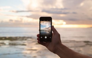 Hand holding a phone with a picture of the beach in front of it on the phone