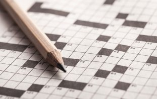 Close up of blank crossword puzzle paper with pencil sitting on it