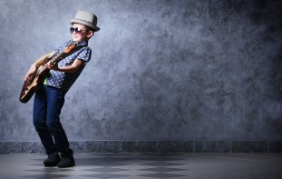 Boy wearing sunglasses and a hat while playing a guitar