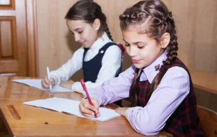 Two young girls sitting at desk in school uniforms writing on paper