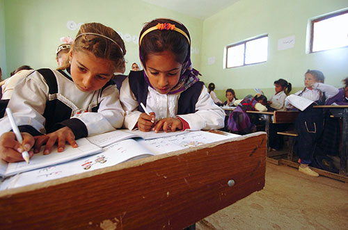 Two young girls at desk working together in a classroom