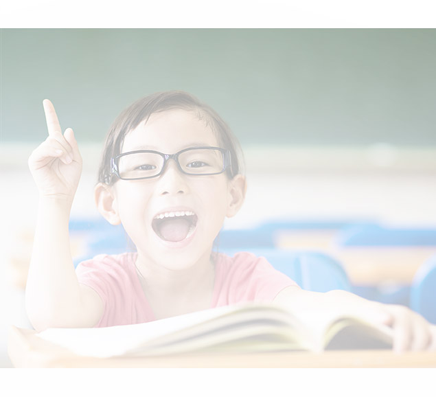 Girl sitting at a desk with a book open excitedly raising her finger
