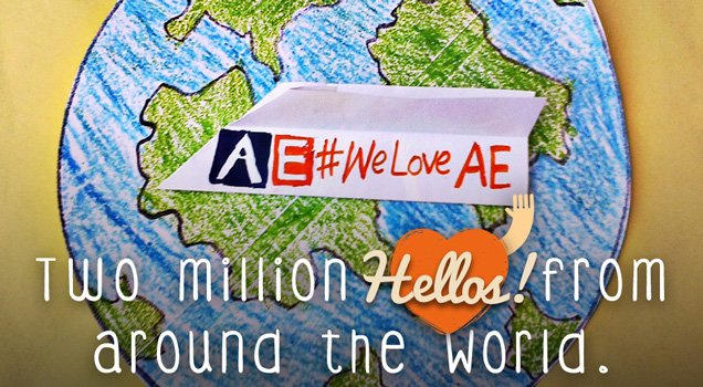 "Paper plane with text ""AEweloveAE"" written on it in front of drawing of the world"