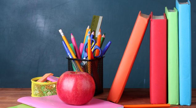 An apple, books, pencils and notebooks sitting on desk