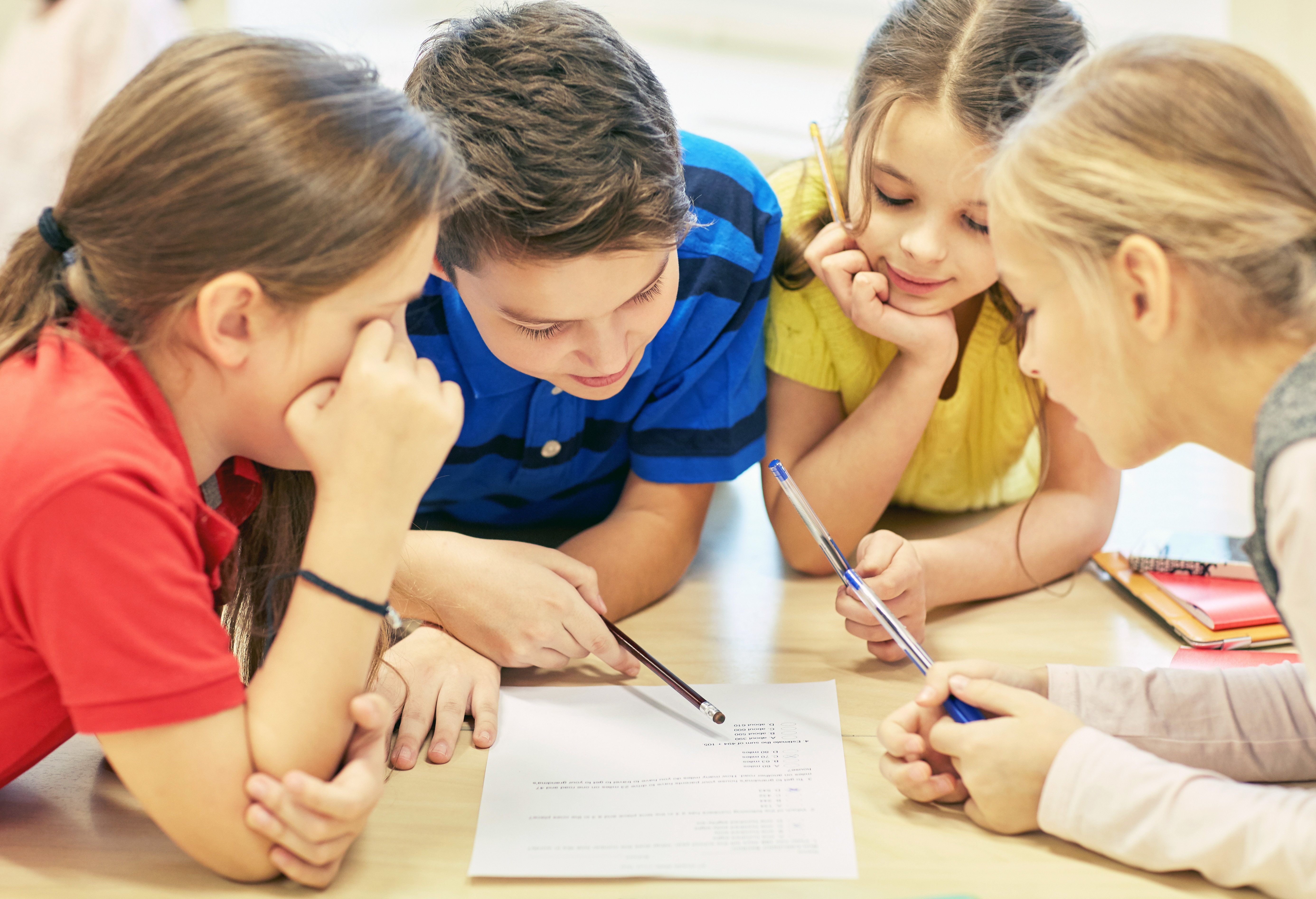 Group of children looking at paper on a desk